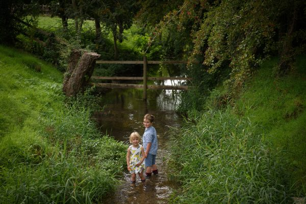 portrait of brother and sister wading in a river