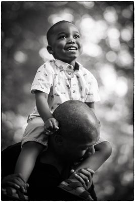 a boy on his fathers shoulders