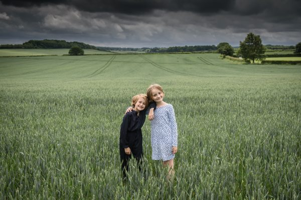 sisters portrait picture taken in green field with storm approaching
