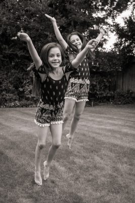 portrait of sisters jumping for joy