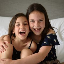 portrait photograph of sisters laughing